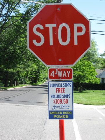 "Photo of stop sign w/ sign that says ""Rolling stops $109.50"""