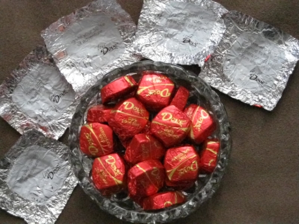 A bowl of Dove chocolates surrounded by their wrappers