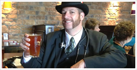 Liam Dempsey raising a pint of beer while dressed as Dr. Watson