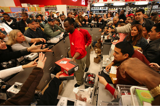 Shoppers surrounding clerk on Black Friday