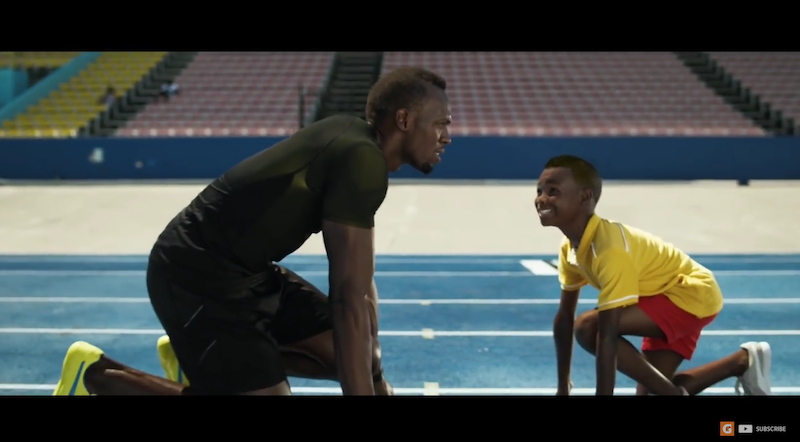screen grab of video with Usain Bolt facing his child self on track